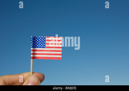 Hand holding small American flag - Stock Photo