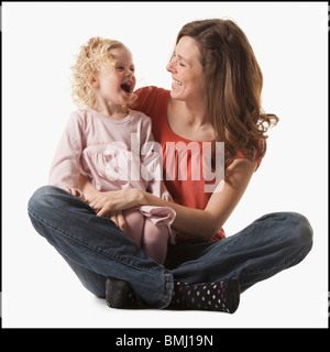 Mother holding daughter in her lap - Stock Photo