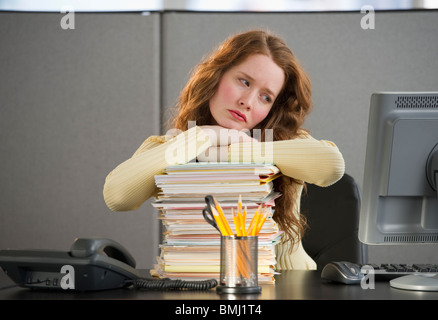 Overworked woman in cubicle - Stock Photo