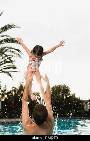 Father and daughter playing in pool - Stock Photo