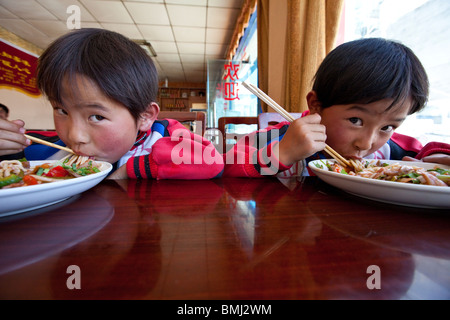 Brothers eating noodles in Shigatse, Tibet - Stock Photo