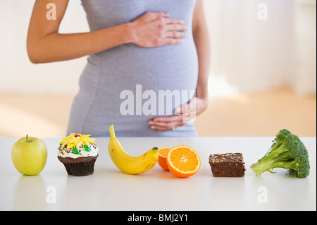 Pregnant woman standing behind a row of food - Stock Photo