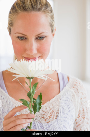 Woman smelling a white flower - Stock Photo