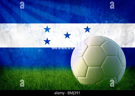 Grunge Honduras flag on wall and soccer ball - Stock Photo
