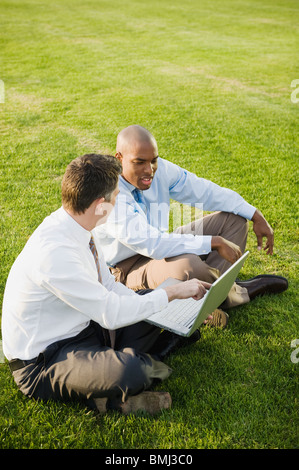 Co-workers sitting on grass - Stock Photo