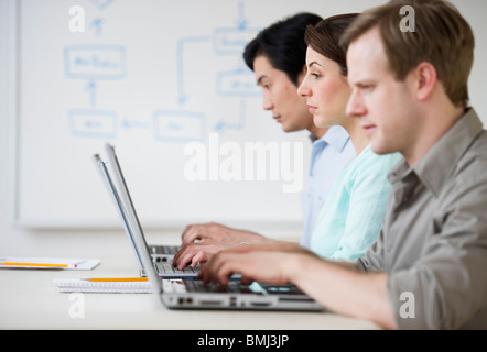 Adults working on laptops in classroom - Stock Photo