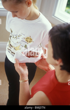 mother and daughter and torn tee shirt - Stock Photo