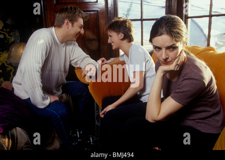 a couple having a drink together in a bar with a woman in the foreground looking fed up - Stock Photo