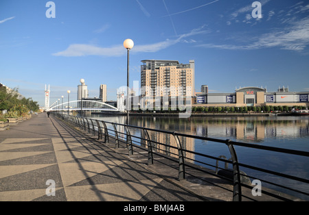 View along the quayside of Salford Quays towards the Millennium footbridge and the Lowry Outlet Mall. - Stock Photo