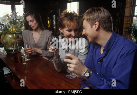 a couple having a drink together in a bar with a woman in the background looking fed up - Stock Photo