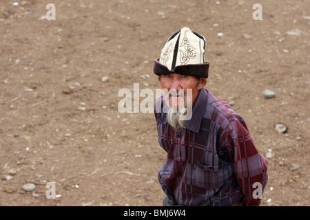 An old Kyrgyz man wearing kalpak at animal market in Karakol, Kyrgyzstan - Stock Photo