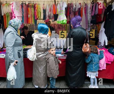 Turkish women buying headscarves at Turkish market on Maybachufer in Kreuzberg district of Berlin Germany - Stock Photo