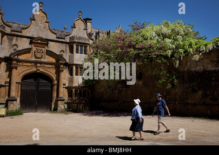 Tourists pass Stanway House in Stanway, The Cotswolds, Gloucestershire, UK. - Stock Photo