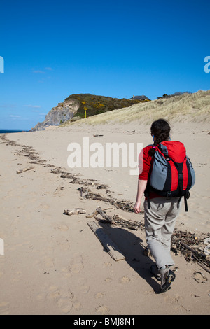Woman hiker walking on beach Caldey Island Wales UK - Stock Photo
