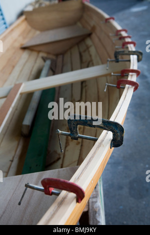 Carpenter presses in the shipyard, holding together the side planks of a scull, Auckland, New Zealand - Stock Photo