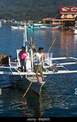 A small boat and CORON TOWN on BUSUANGA ISLAND in the CALAMIAN GROUP - PHILIPPINES - Stock Photo