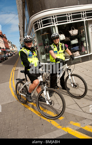 Two policemen patrolling on bicycles, Aberystwyth Wales UK - Stock Photo