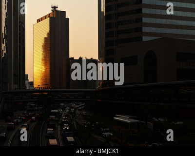 Last ray of sunset reflected on a skyscraper in Central Financial district in Hong Kong, with busy commuters on - Stock Photo