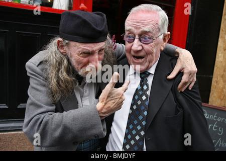 Two Friends outside a Pub, Glasgow, Scotland - Stock Photo