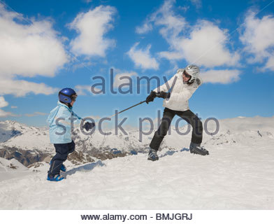 Woman pulling boy up snowy hill - Stock Photo