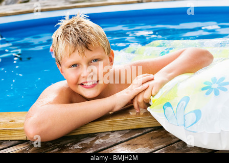 Boy bathing in outdoor pool - Stock Photo