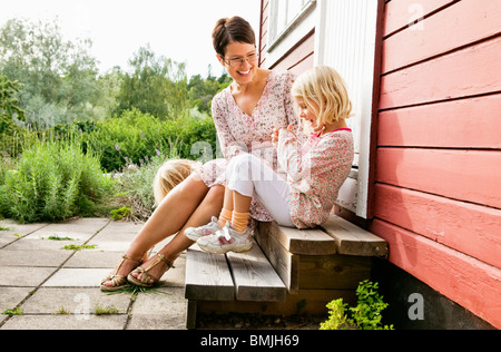 Mother and daughters sitting on stair - Stock Photo