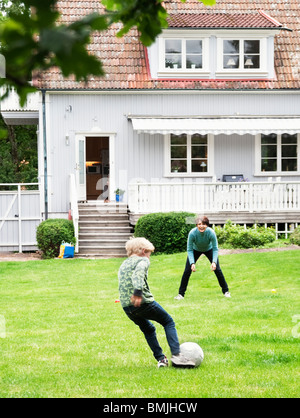 Mother and son playing soccer in garden - Stock Photo