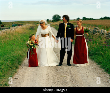 Scandinavia, Sweden, Oland, Bride and groom with bridesmaid and flower girl - Stock Photo