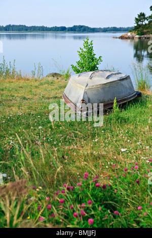 Stranded boat by lake - Stock Photo