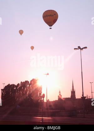Scandinavia, Sweden, Stockholm, Sodermalm, Slussen, Silhouette of hot air balloons in sky (lens flare) - Stock Photo