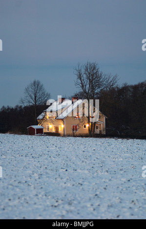 View of house on snow covered landscape - Stock Photo