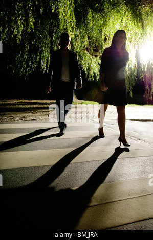 Couple crossing road at night - Stock Photo