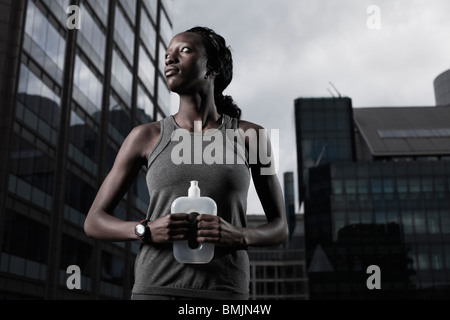 Fit young woman dressed in sportswear and holding water bottle backgrounded by modern city buildings - Stock Photo