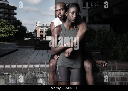 Man & woman in sports wear outdoors at city estate - Stock Photo