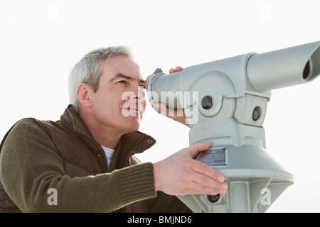 Man looking through a telescope - Stock Photo