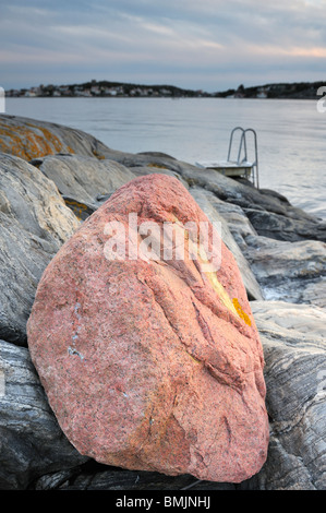 Red stone on flat rocks - Stock Photo