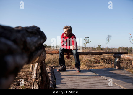 Man relaxing on wooden bench - Stock Photo