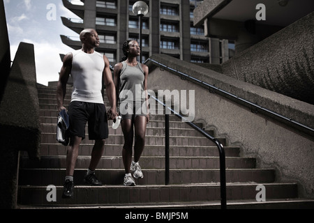 Young fit couple walking down stairway on city estate early morning - Stock Photo