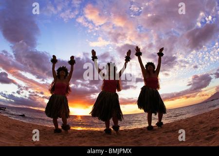 Three hula dancers at sunset at Palauea Beach, Maui, Hawaii, USA. - Stock Photo