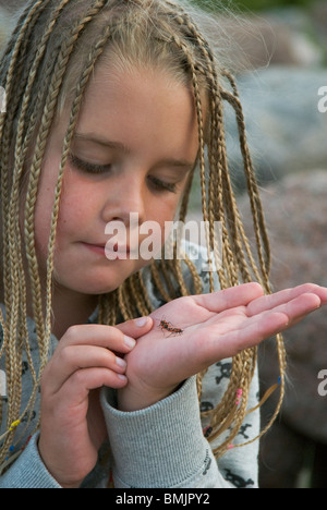 Scandinavia, Sweden, Smaland, Girl (6-7) with holding bug on palm, close-up - Stock Photo