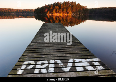Pier on lake with trees reflecting in water - Stock Photo
