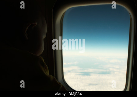 A baby looking out of a window in a plane - Stock Photo