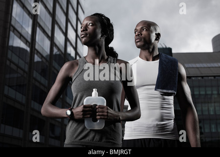 Athletic man and woman dressed in sportswear backgrounded by modern city buildings - Stock Photo