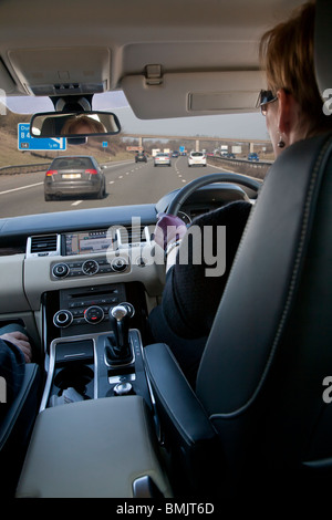 Interior of Range Rover car being driven by woman on motorway in UK, man passenger, with sat nav on dashboard and - Stock Photo