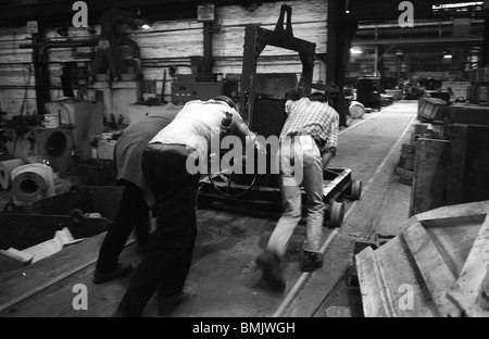 Workers pushing trolley of molten metal in Black Country foundry, West Midlands, England - Stock Photo