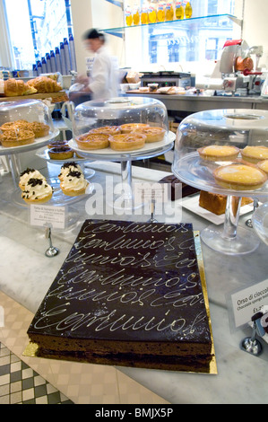 A Carluccio's cake and display of other cakes, buns and pastries for sale ready to be consumed in a Carluccio restaurant - Stock Photo
