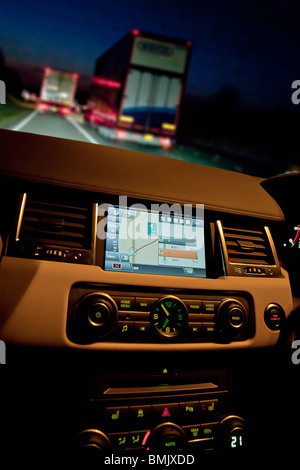 Interior of Range Rover car showing sat nav and dials on dashboard at night on motorway with traffic. UK - Stock Photo