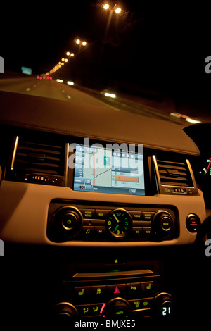 Interior of Range Rover car showing sat nav and dials on dashboard at night on motorway. UK - Stock Photo