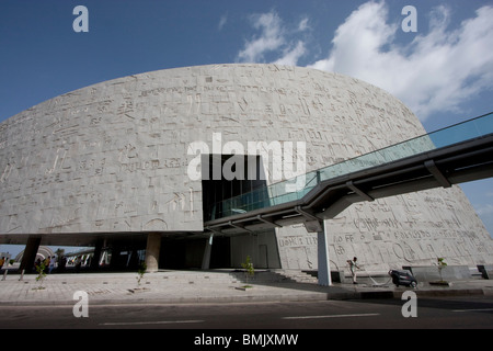 Exterior view from south, showing granite wall of the Bibliotheca Alexandrina, pierced by pedestrian bridge, Alexandria, - Stock Photo