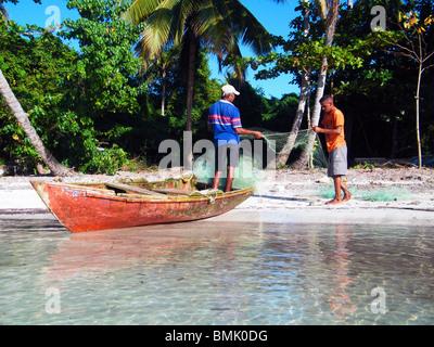 Fishermen mend their nets on La Playita beach, Dominican Republic - Stock Photo